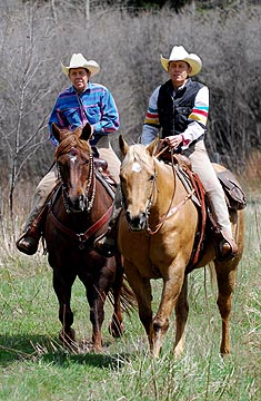 Twin Wranglers ride down a trail