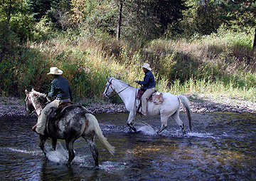 Twin Wranglers riding across the Fisher River